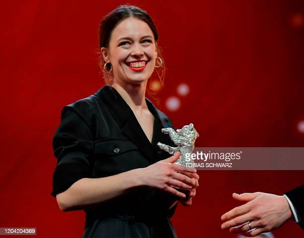 German actress Paula Beer reacts with the trophy Silver Bear for Best Actress during the awarding ceremony of the 70th Berlinale film festival in...