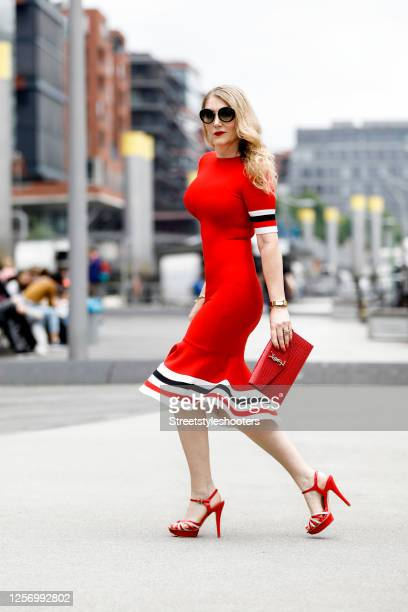 German actress Sandra Quadflieg, wearing a red dress with a red-blue-white curled braid, red high heels by Vera Pelle, a red bag by YSL, a golden...