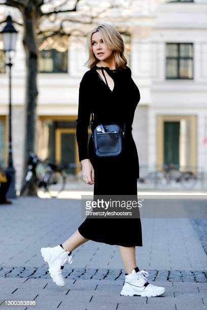 German actress Veronica Ferres wearing a black bag by Montblanc, white sneaker by Kennel&Schmenger and a long black dress by Cos during a street...