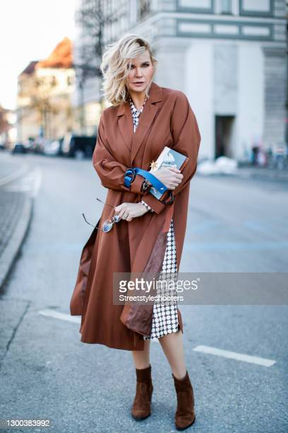 German actress Veronica Ferres wearing a midi length brown and white polka dot wrap dress by Marina Rinaldi, brown boots by Tory Burch, a...