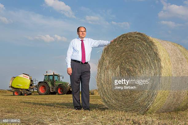 German Agriculture and Consumer Protection Minister Christian Schmidt poses next to a straw bale while he attends hay harvest in on August 01 2014 in...
