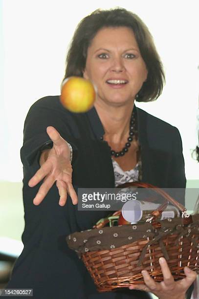 German Agriculture and Consumer Protection Minister Ilse Aigner tosses an apple to photographers after receiving a bsket from regional Harvest Queens...