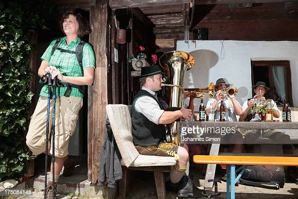 German Agriculture Minister Ilse Aigner listens to brass musicians as she arrives at an alpine alm during a hike in the Traunstein region of the...