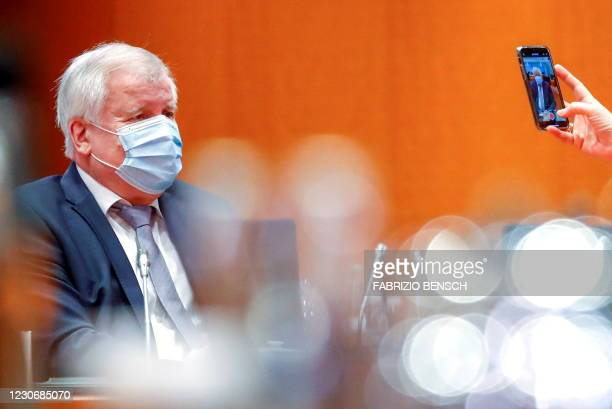 German Agriculture Minister Julia Kloeckner holds a phone to record German Interior Minister Horst Seehofer as they attend the weekly cabinet meeting...