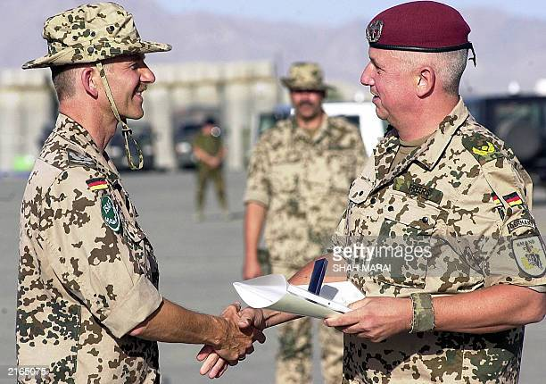 German Air Force Colonel Martin Schelleis receives a medal for his service in Afghanistan from German Brigadier General Werner Freers during a...