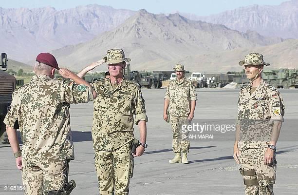 German Air Force Colonel Uwe Aherns salutes German Brigadier General Werner Freers as German Colonel Martin Schelleis looks on during a ceremony...