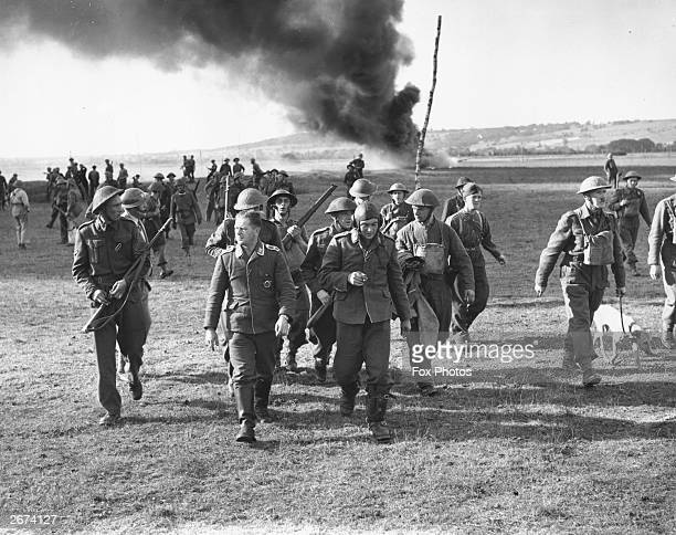 German airmen who parachuted from a shotdown Heinkel HE111 bomber are marched off by the Home Guard in Goodwood Sussex