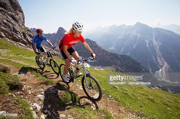 German Alps, Karwendel, young couple mountain biking