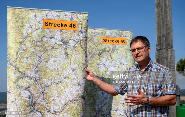 German amateur historian Dieter Stockmann poses next to a map featuring the Route 46, an abandoned motorway from the Nazi era, on August 21, 2019...