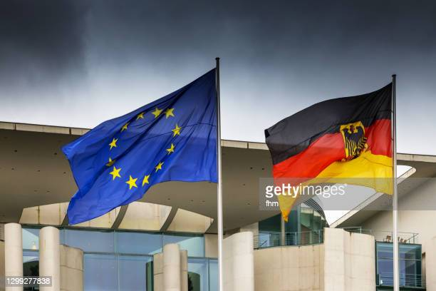 german and eu-flag with german chancellery and dark clouds - german chancellery stock pictures, royalty-free photos & images