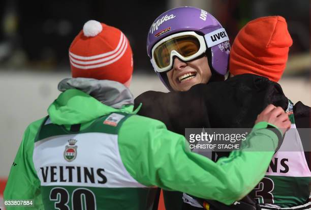 German Andreas Wellinger his compatriot 's Richard Freitag and Markus Eisenbichler celebrate after the FIS ski jumping World Cup flying hill...