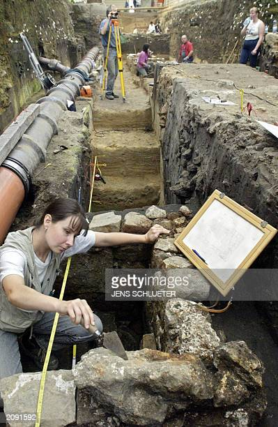 German archaeologist Caudian Hartung examines 04 June 2003 a stone burial chamber discovered in an archaeological site in Magdeburg Archaeologists...