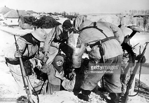 German army soldiers help a woman to leave an underground shelter in a village in the Kharkiv area Ukraine February 1943