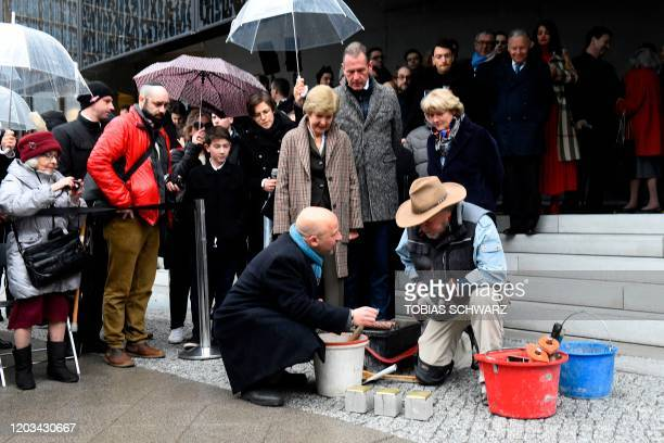 German artist Gunter Demnig is assisted by Bobby Lax , descendant of Holocaust victims, as he lays stumbling stones during a ceremony in front of the...
