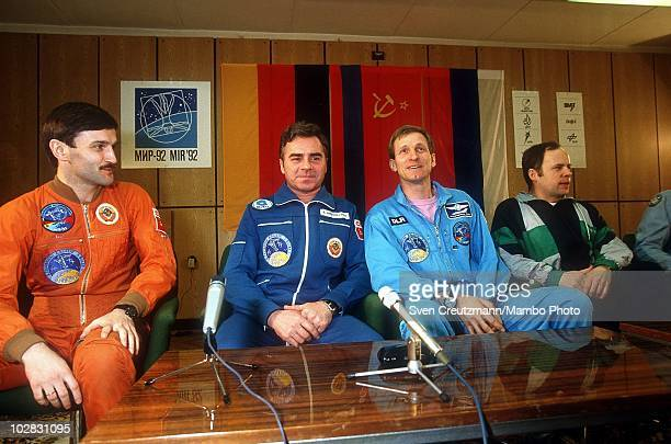 German astronaut Klaus Dietrich Flade and Russian cosmonauts Aleksandr Kaleri and Aleksandr Viktorenko sit behind a wall of glass as they give a...
