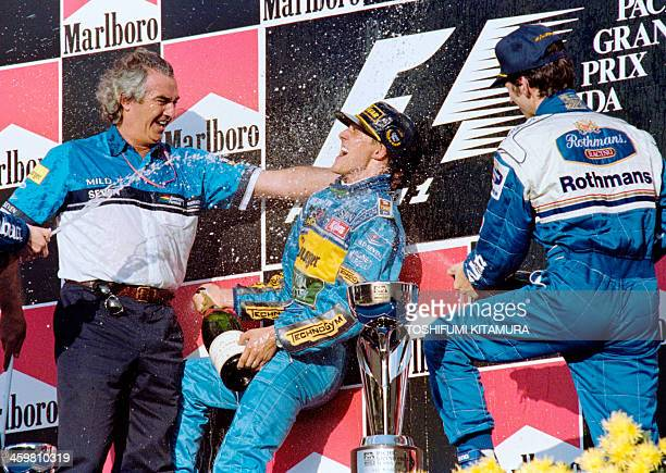 German Benetton-Renault driver Michael Schumacher jubilates on the podium, with Flavio Briatore, manager of Benetton-Renault team, after winning the...