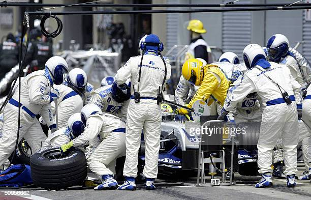 German BMW Williams F1 driver Ralf Schumacher is surrounded by crew members during a pit stop in the 2004 Grand Prix of Canada 13 June at the Circuit...