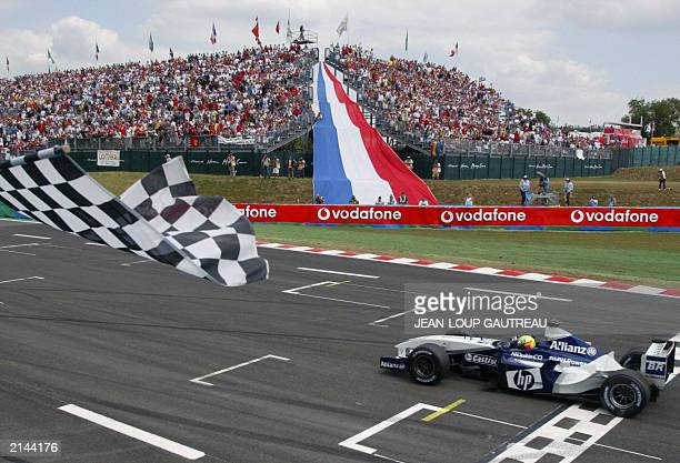 German BMWWilliams driver Ralf Schumacher crosses the finish line of the MagnyCours racetrack 06 July 2003 at the end of the Formula One Grand Prix...