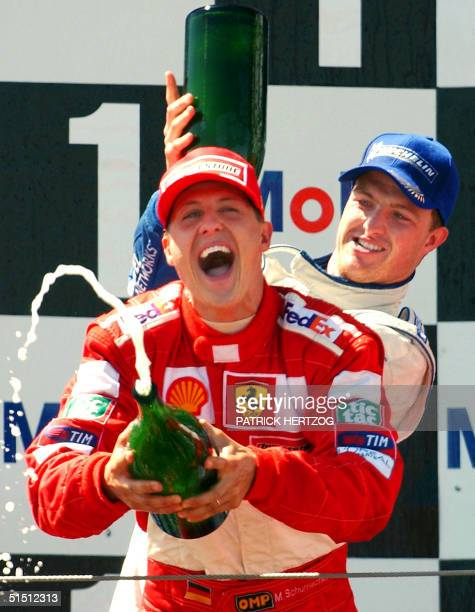 German BMWWilliams driver Ralf Schumacher sprays champagne on his brother Ferrari driver Michael on the podium of the MagnyCours racetrack 01 July...