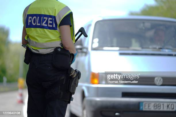 German border police officer stops cars in a checkpoint of the D87 road at the German-French border during the coronavirus crisis on May 8, 2020 near...