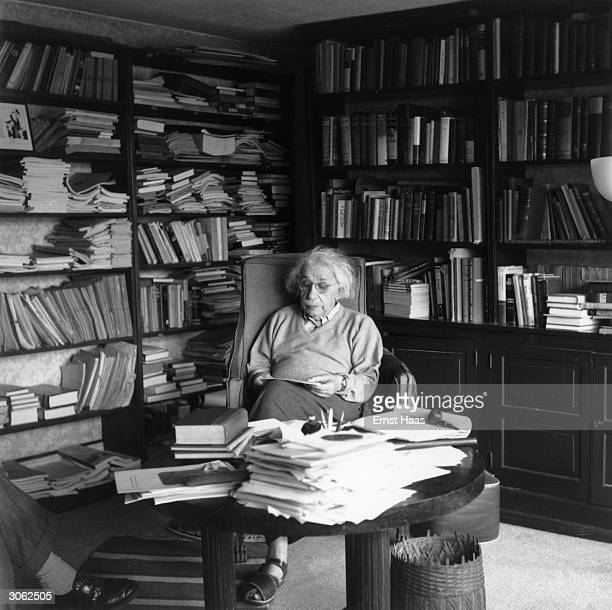 German born physicist who formulated the theories of relativity, Albert Einstein ponders a problem in his paper-filled study in Princeton, New...