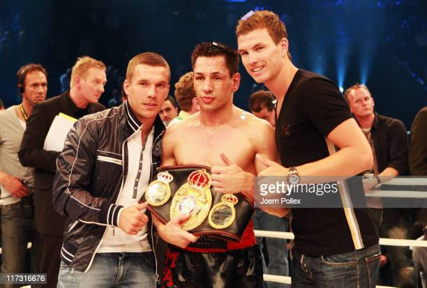 German boxer Felix Sturm celebrates with soccer player Lukas Podolski and Edin Dzeko after winning the WBA Super World middleweight title fight at...