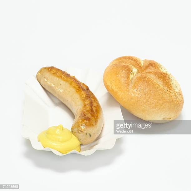 German Bratwurst, fried sausage and bread with mustard in paper plate