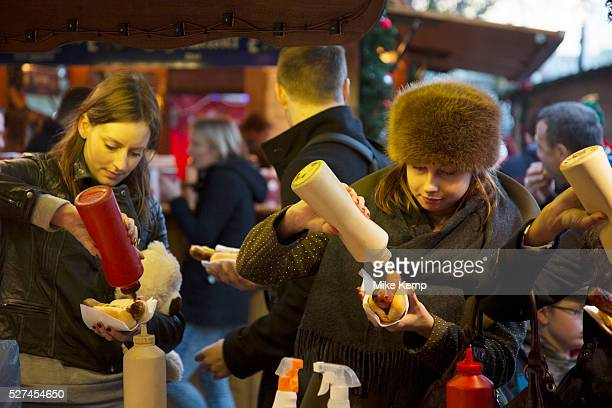 German bratwurst stall at the Christmas market doing a roaring trade as people queue for the grilled sausages and squeeze ketchup and mustard onto...