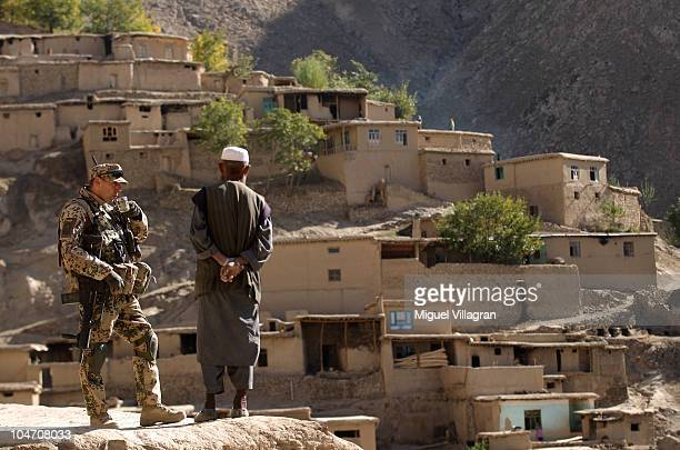 German Bundeswehr soldier drinks a cup of tea with a man during a patrol on October 4 2010 in KhamiAwwal Afghanistan Germany has more than 4500...
