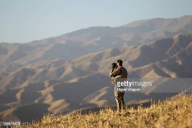 German Bundeswehr soldier looks through binoculars as he patrols high ground overlooking the city on October 2 2010 in Feyzabad Afghanistan Germany...