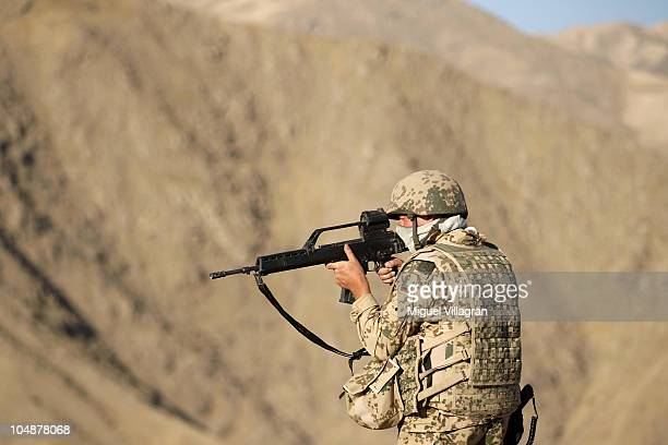 German Bundeswehr soldier looks through the binoculars of his rifle as he patrols high ground overlooking the city on October 2 2010 in Feyzabad...