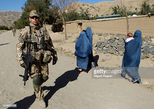 German Bundeswehr soldier patrols a street as women walk past on October 2 2010 in Feyzabad Afghanistan Germany has more than 4500 military forces in...
