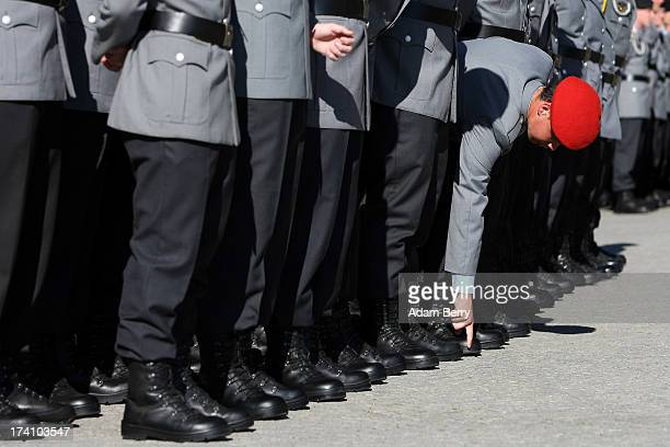 German Bundeswehr soldier recruit rubs a spot on his shoe at the last moment prior to the start of a swearingin ceremony for new recruits of the...