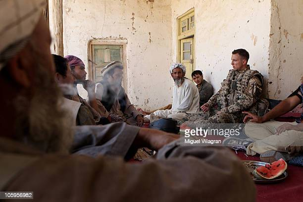 A German Bundeswehr soldier talks to the inhabiters of a small village on October 17 2010 near MazareSharif Afghanistan Germany has more than 4500...