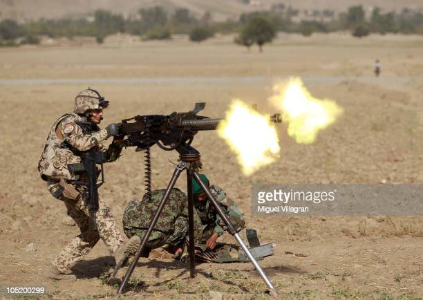 German Bundeswehr soldiers of a OMLT unit fire a machine gun during a training session with Afghan National Army soldiers on October 12 2010 in...