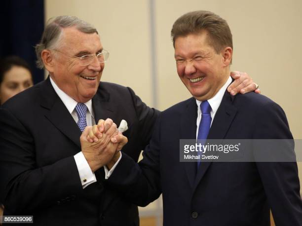 German businessman CEO of TUI AG Klaus Mangold embrasses Gazprom's CEO Alexey Miller during a meeting with German businessmen October 12 2017 in...