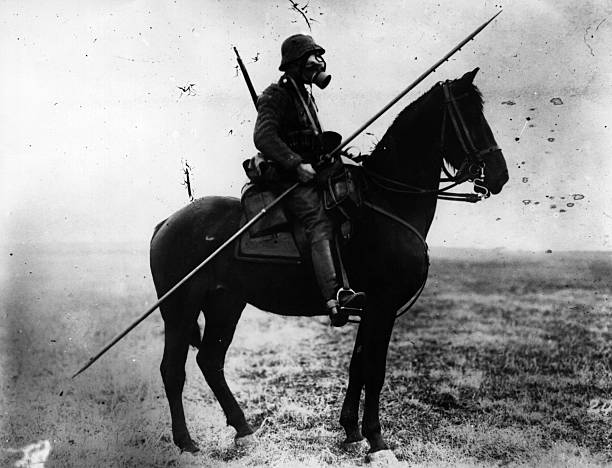 A German cavalryman wearing a gas mask and carrying...