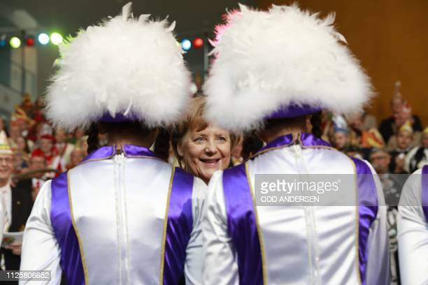 TOPSHOT German Chacellor Angela Merkel talks to a carnival group during a carnival reception at the chancellery in Berlin on February 19 2019 German...
