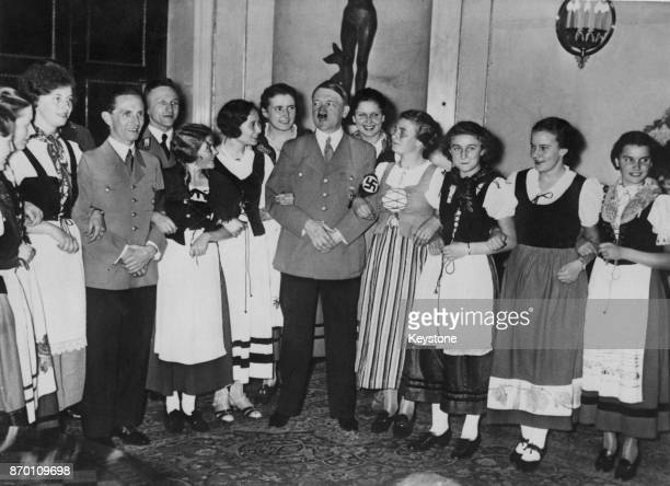 German Chancellor Adolf Hitler and a group of young women from the Rhineland in national costumes visit Propaganda Minister Joseph Goebbels at the...