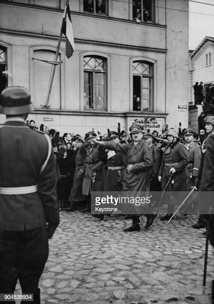 German Chancellor Adolf Hitler gives the Nazi salute whilst inspecting German troops in the Theatre Square in Memel, Germany , March 1939. The troops...