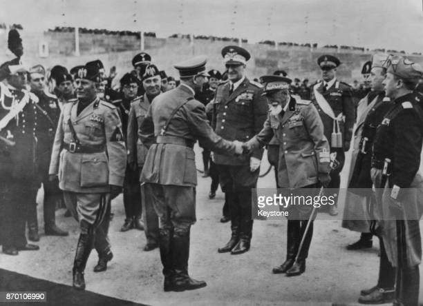 German Chancellor Adolf Hitler is greeted by Italian Marshal Emilio De Bono upon his arrival at the Francesco Baracca Aerodrome in Rome Italy to...