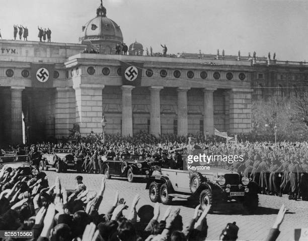 German Chancellor Adolf Hitler is saluted by the crowds as he makes his way to the great parade of troops in Vienna Austria 15th March 1938