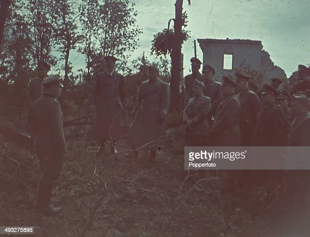 German Chancellor Adolf Hitler Italian Prime Minister Benito Mussolini and Field Marshal Wilhelm Keitel talk with German officers on the Eastern...