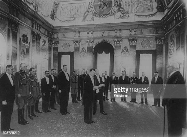 German Chancellor Adolf Hitler reading the good wished of the government to President Paul von Hindenburg , watched by Vice Chancellor Franz von...