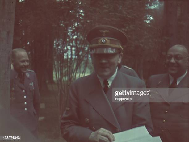 German Chancellor Adolf Hitler reads official papers with his personal physician Theodor Morell in attendance on far right