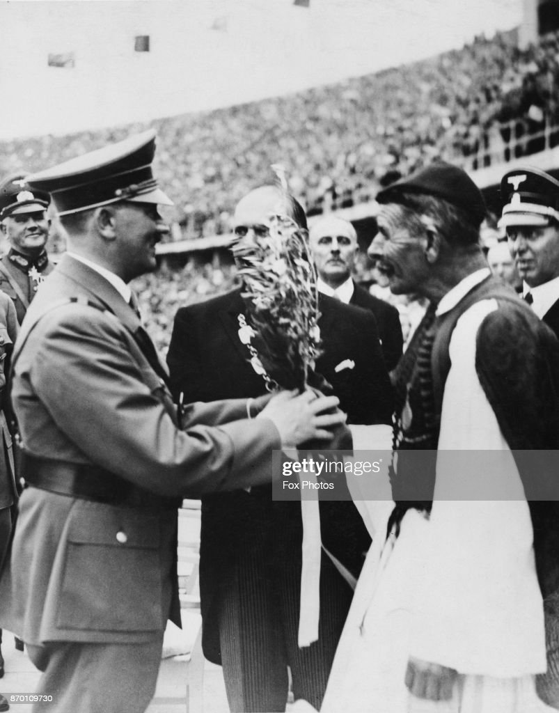 German Chancellor Adolf Hitler (1889 - 1945) receives the Olympic Olive Branch from Spyridon Louis (1873 - 1940, right) at the Olympic Stadium, at the opening of the Berlin Olympics, Germany, 1st August 1936. Louis won the Olympic marathon at the 1896 Summer Olympics.