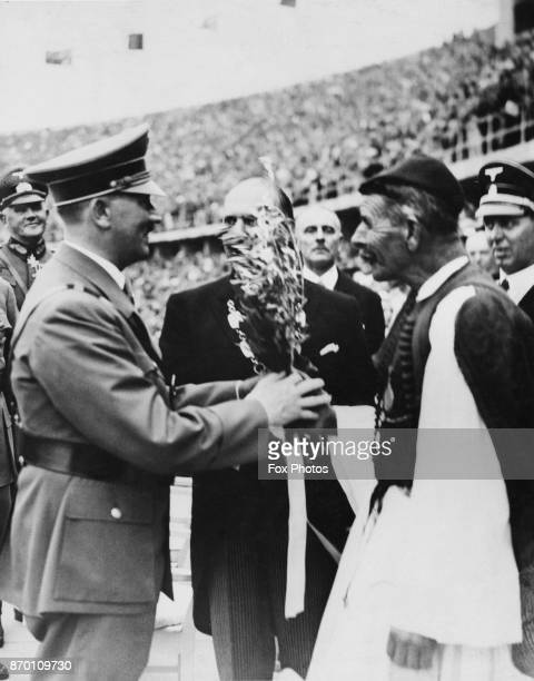 German Chancellor Adolf Hitler receives the Olympic Olive Branch from Spyridon Louis at the Olympic Stadium at the opening of the Berlin Olympics...