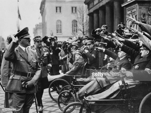 German Chancellor Adolf Hitler receives the salute from a group of injured war veterans during a ceremony at the War Memorial in Berlin, Germany, 8th...