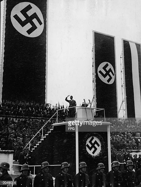 German chancellor Adolf Hitler salutes crowds from a podium draped in swastika banners during a May Day Nazi rally at Templehof Airport Berlin...