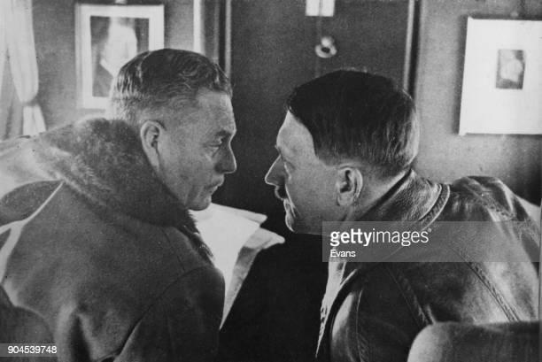 German Chancellor Adolf Hitler speaking conspiratorially to German officer Wilhelm Keitel on board Hitler's private aircraft circa 1942